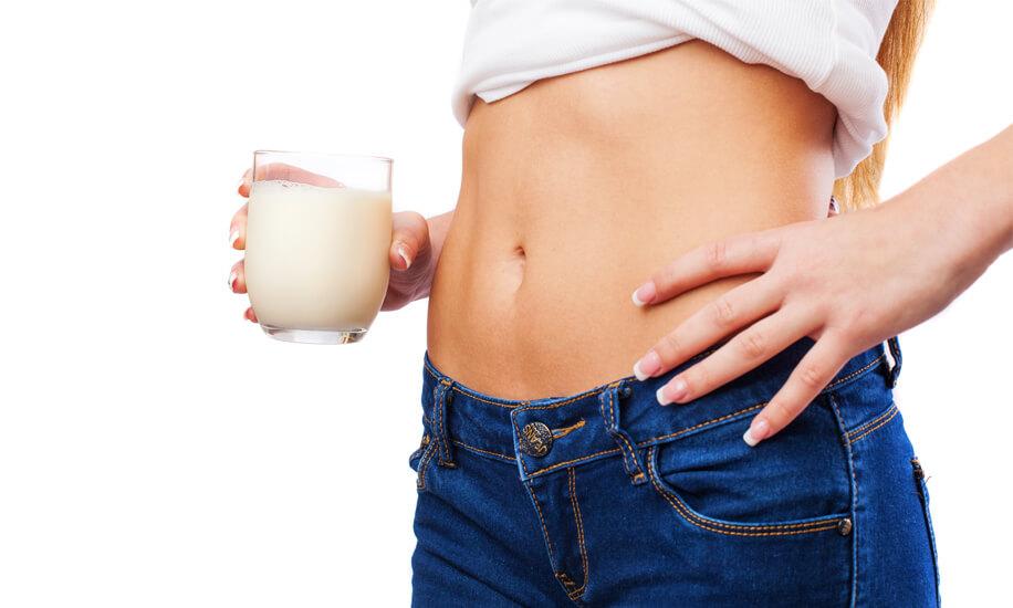 Fit devojka drži čašu mleka